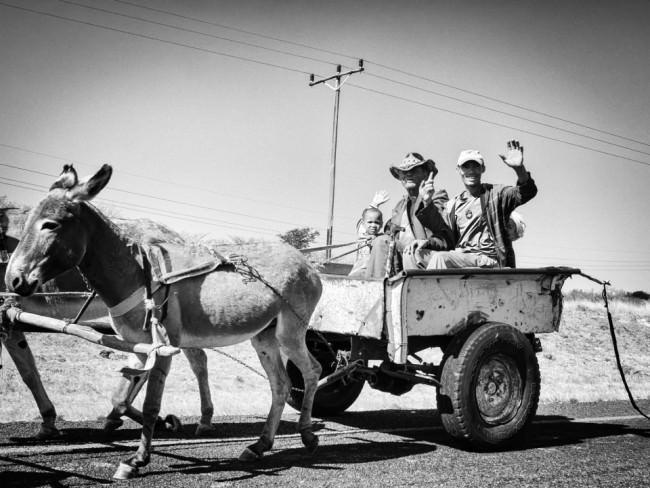Ein paar Menschen sitzen in im einfachen Anhänger eines Eselkarrens, einer winkt.