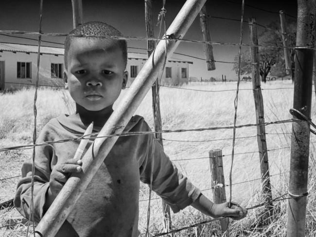 Ein kleiner Junge steht an einem Maschenzaun, hinter ihm erstreckt sich ein Feld, auf dem eine Baracke steht.