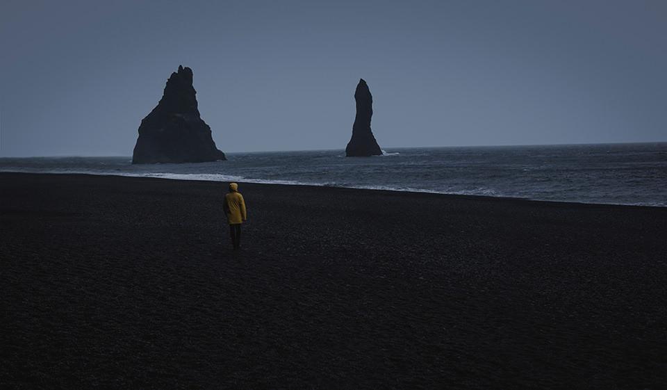 Ein Mann mit gelber Regenjacke am Strand