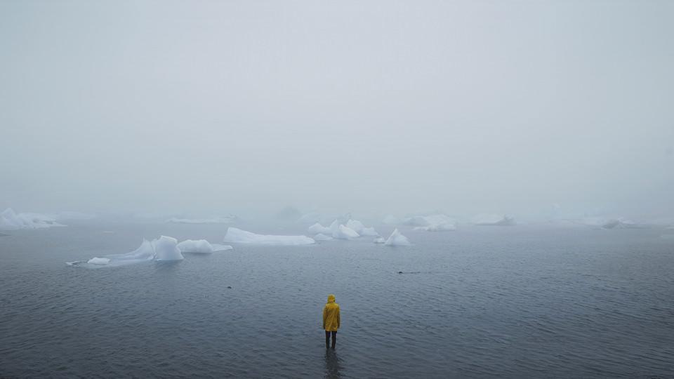 Ein Mann mit gelber Regenjacke im Wasser