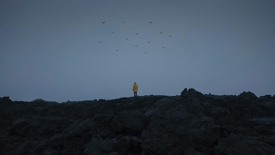 Ein Mann in gelber Regenjacke auf schwarzem Gestein