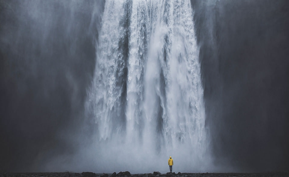 Ein Mann mit gelber Regenjacke vor einem Wasserfall