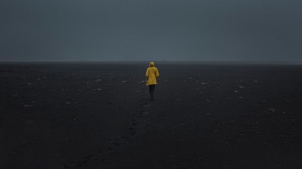 Ein Mann mit gelber Regenjacke rennnt auf schwarzem Boden
