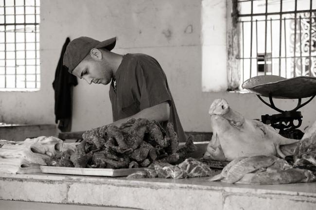 Ein Mann mit Basecap bearbeitet das Fleisch eines Schweines.