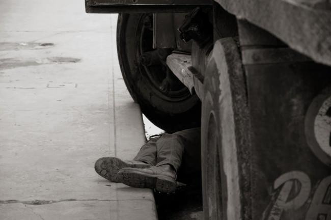 Beine ragen unter einem Auto hervor.