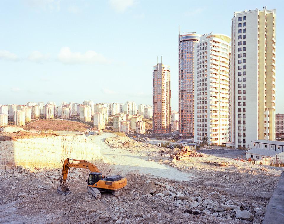 Ein Bagger auf einer Baustelle, im Hintergrund Hochhäuser.