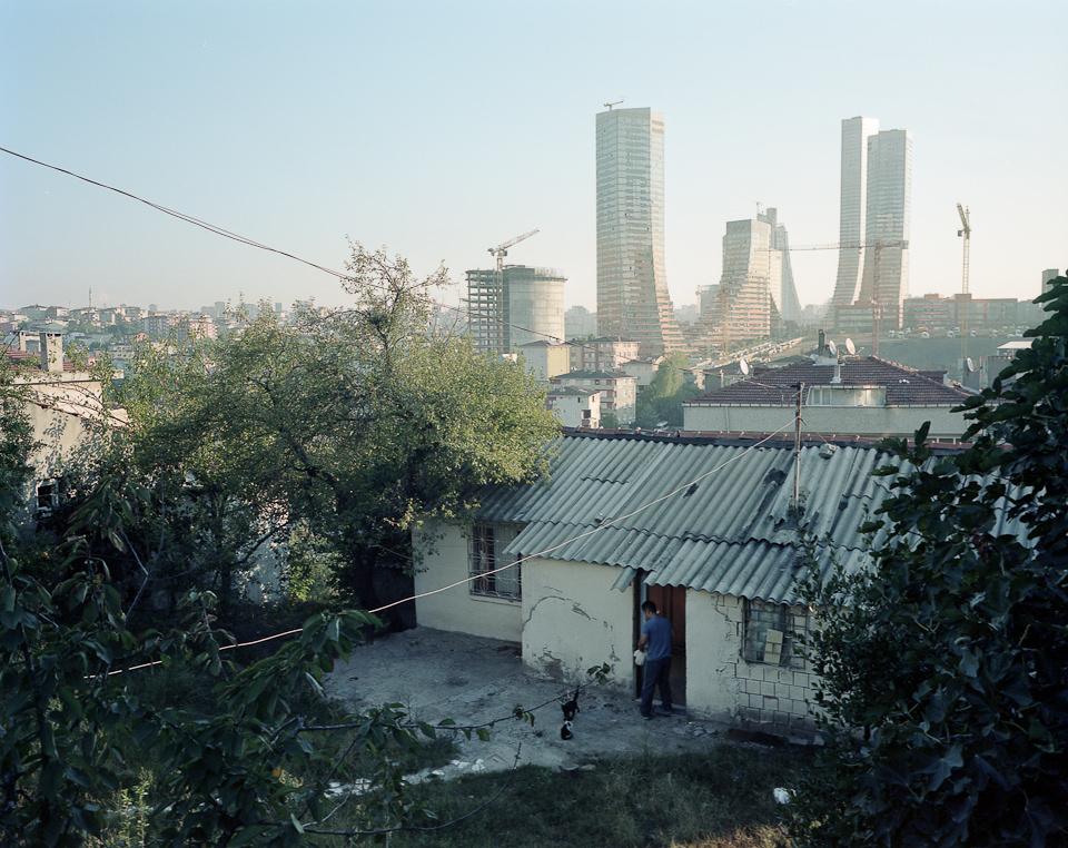 Im Vordergrund ein informelles EInfamilienhaus, im Hintergrund Hochhäuser.