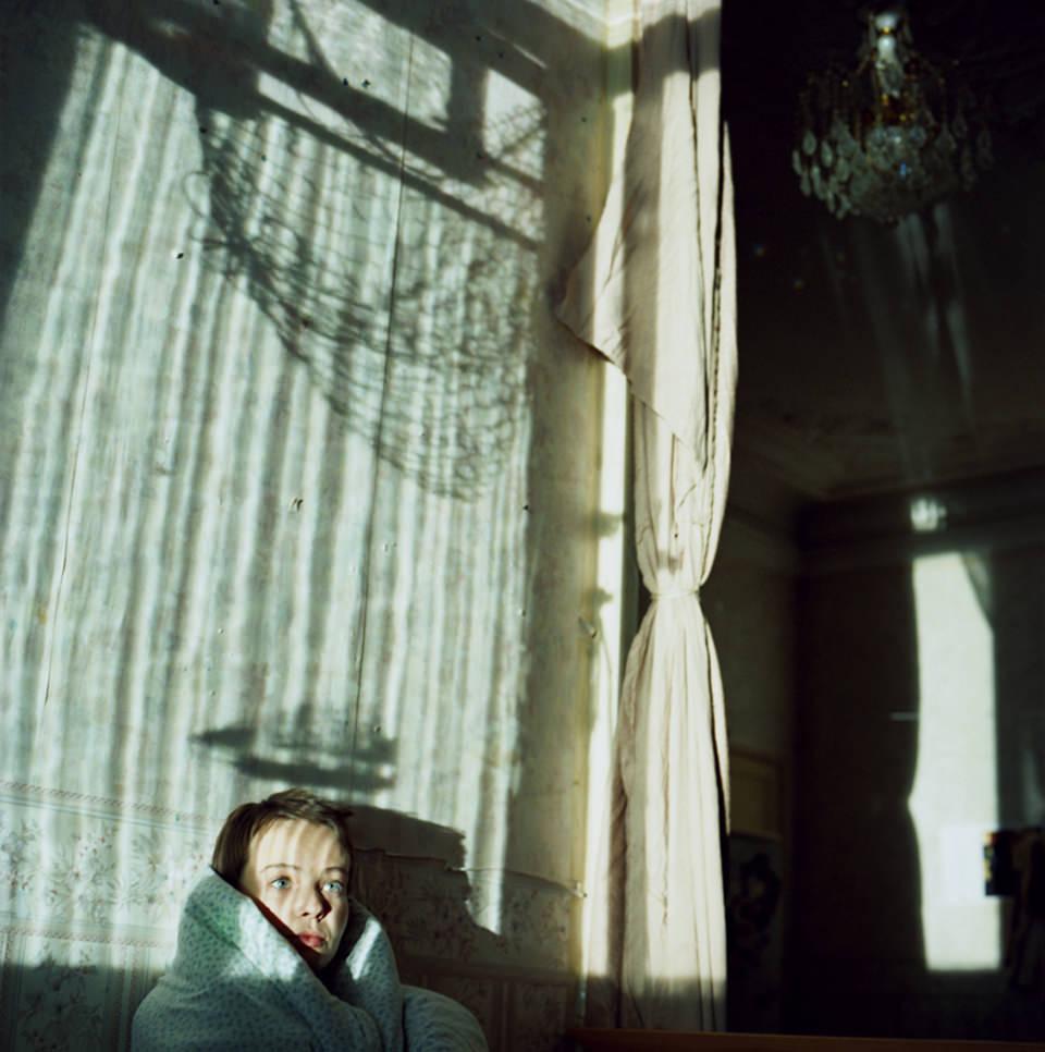 Eine Frau sitzt vor einer Wand mit verschiedenen Schattenspielen