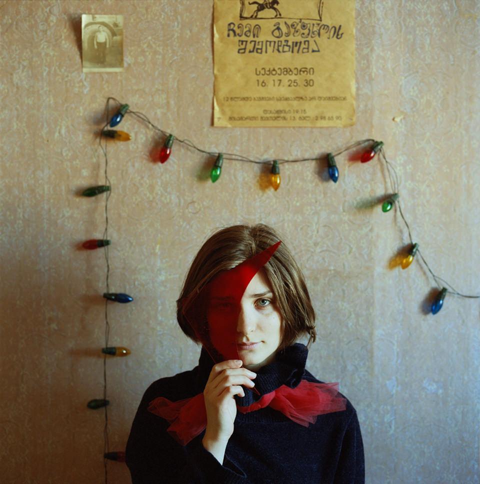 Eine Frau vor einer Wand mit bunter Lichterkette hält sich ein rotes Stück Glas vor das Auge