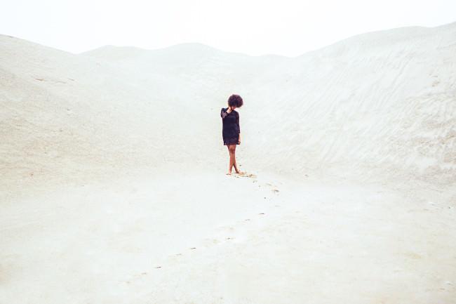 Eine Frau in schwarzem Kleid in der Wüste
