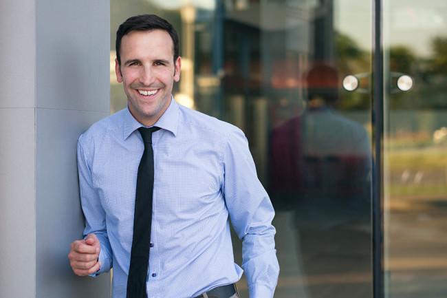 Ein Mann mit Hemd und Krawatte lacht