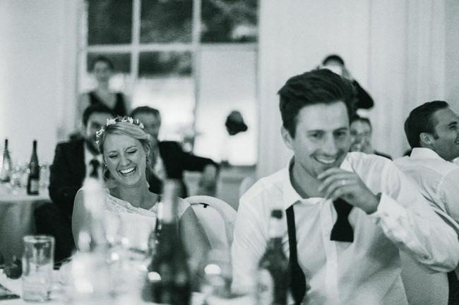 Ein Hochzeitspärchen am Tisch lacht.