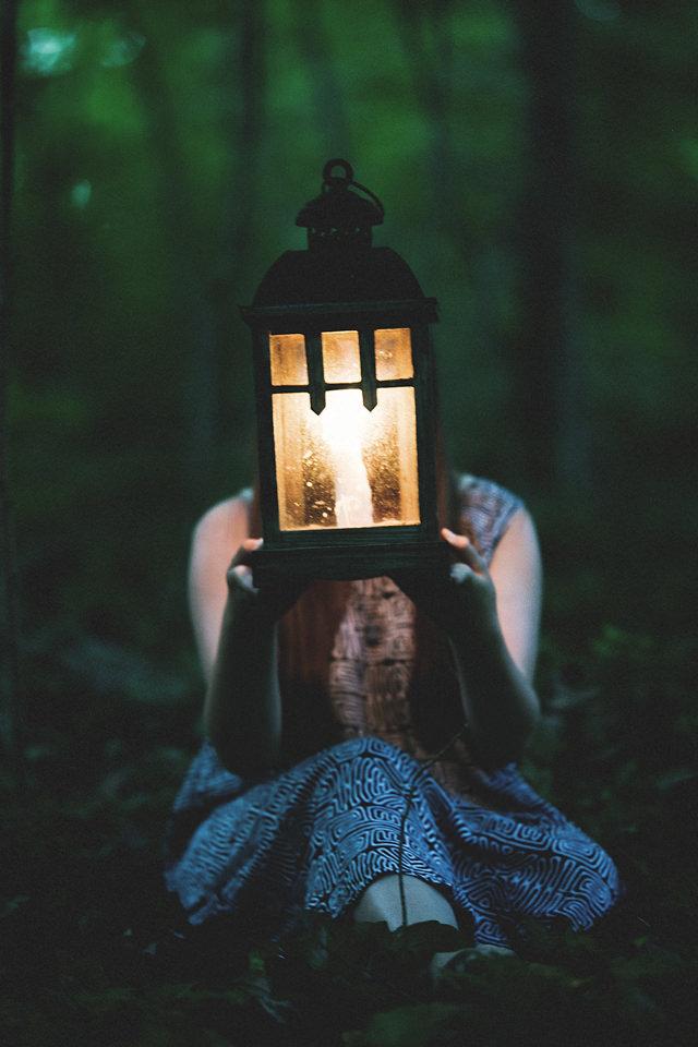 Eine junge Frau sitzt mit einer Laterne im Wald