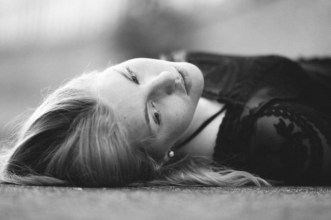 Eine junge Frau liegt auf einer Straße