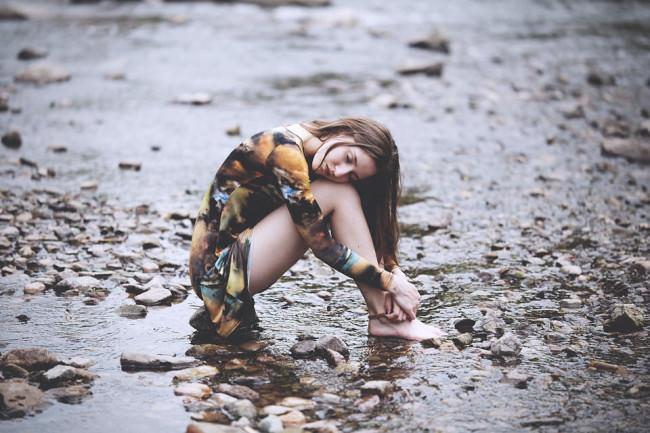 Eine junge Frau sitzt in einem Flussbett