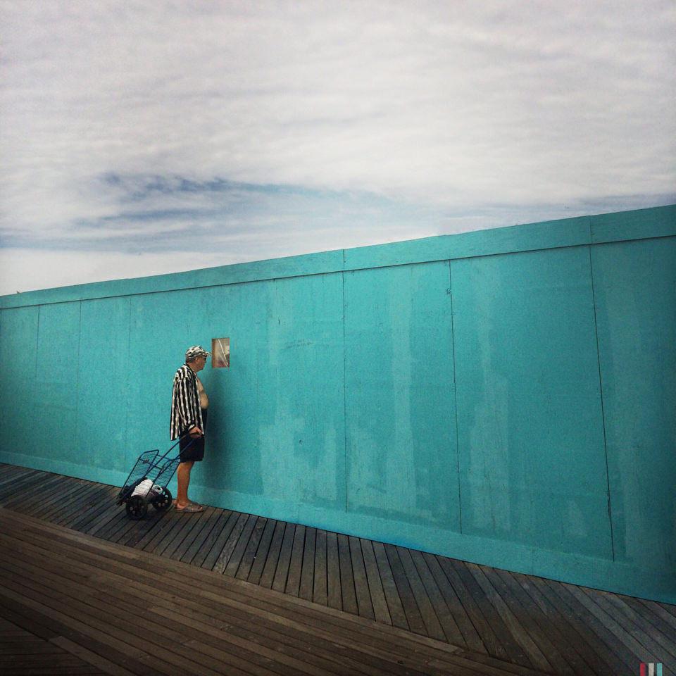 Ein Mann schaut durch einen Zaun
