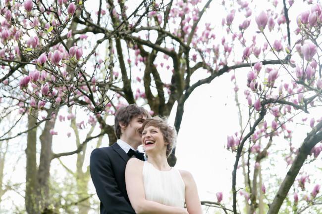 Ein Hochzeitspärchen vor einem blühenden Baum.