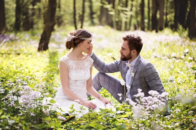 Ein Brautpaar sitzt auf einer Blumenwiese