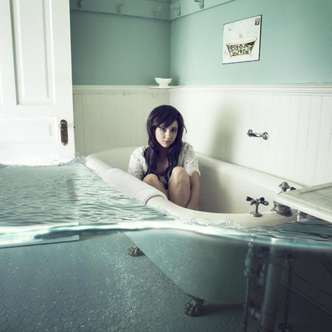 Eine Frau sitzt in einer leeren Badewanne, die von Wassermassen umgeben ist.