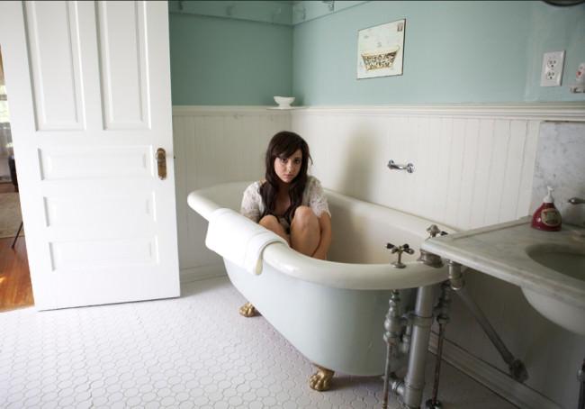 Eine Frau sitzt in einer leeren Badewanne in einem alten Badezimmer.