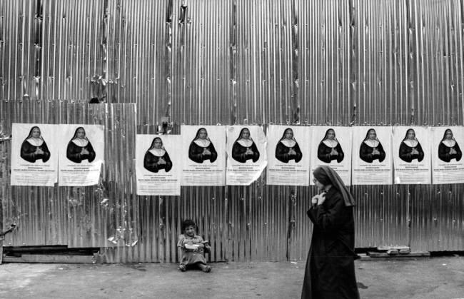 Eine Nonne, die an mehreren Bildern mit Nonnen vorbeigeht