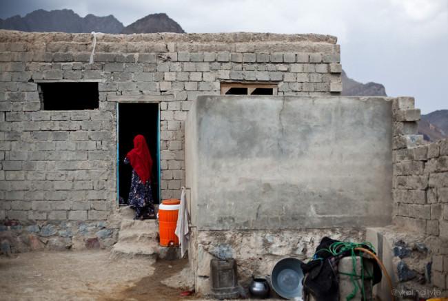 Eine Frau steht im Eingang eines einfachen Hauses.