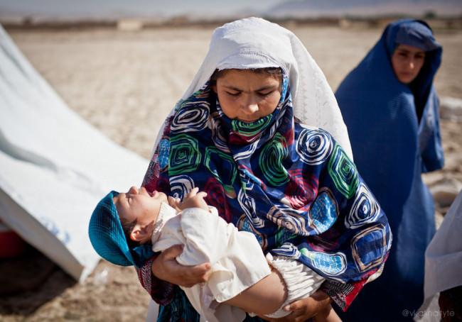 Eine Frau trägt ein Baby.