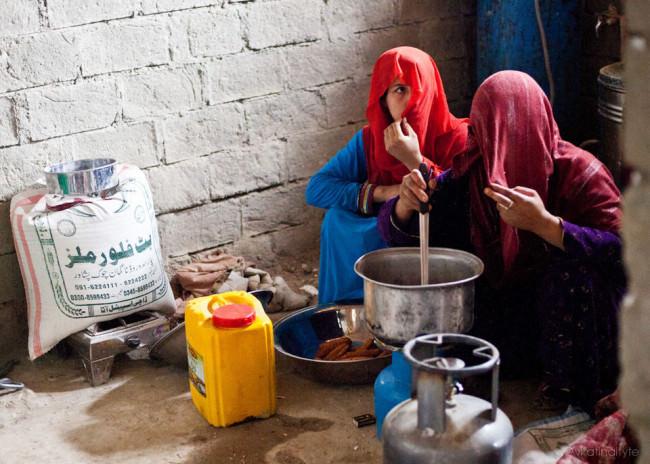 Zwei Frauen sitzen am Boden und kochen.