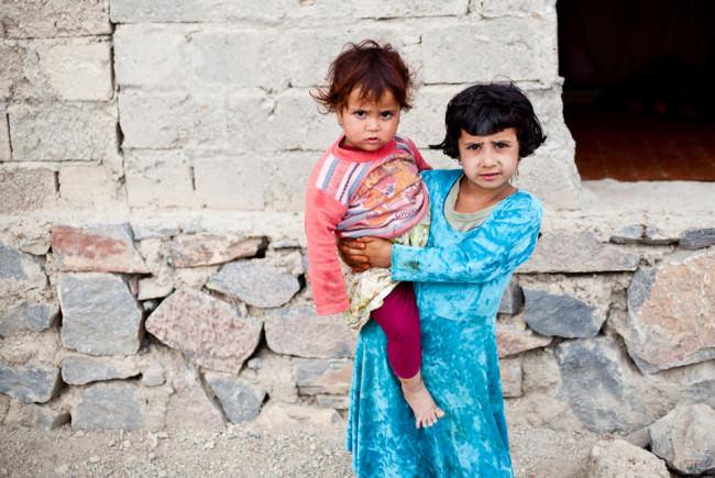 Zwei Kinder vor einer Mauer