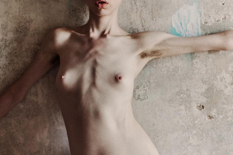 Eine Frau, nackt, barbusig, vor einer Wand.