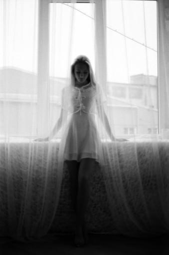 Eine junge Frau steht vor einem Fenster