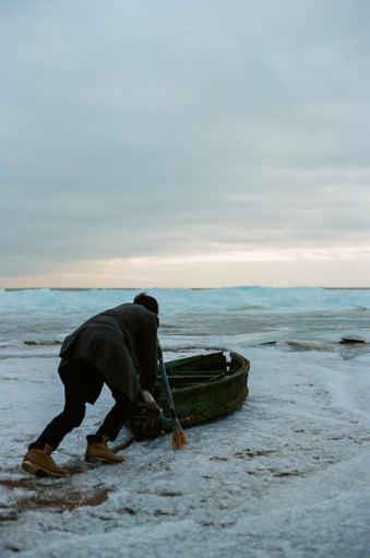 Eine Person schiebt ein kaputtes Boot