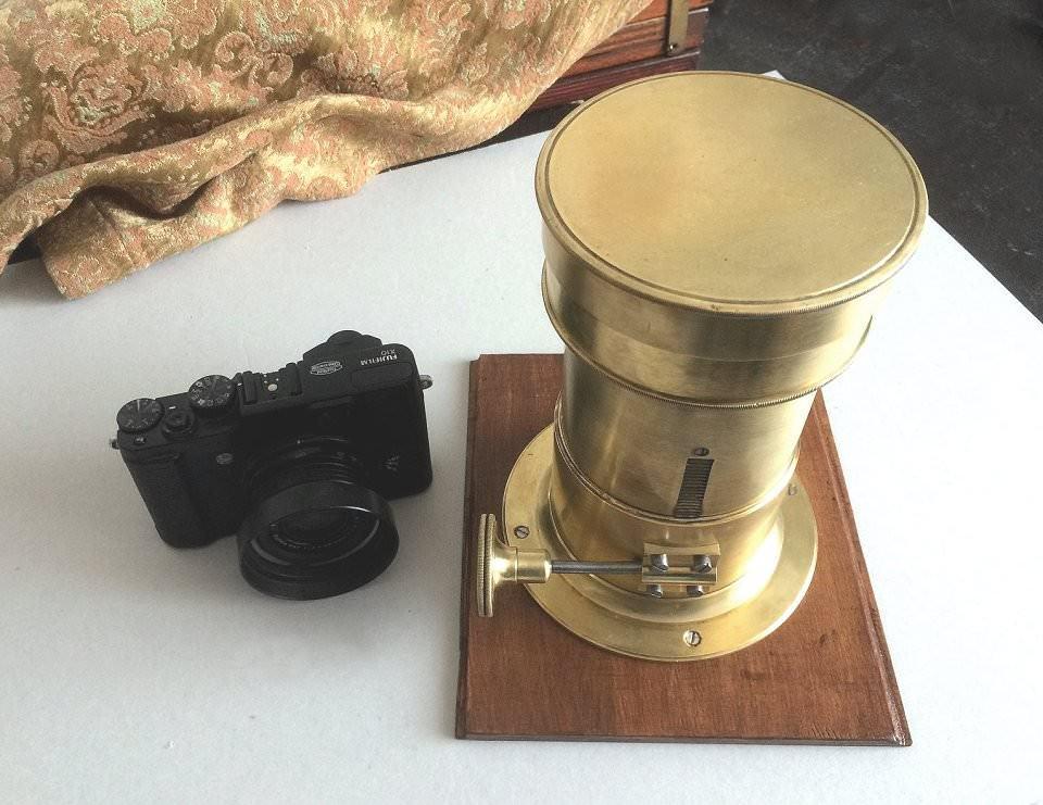 Eine digitale kamera neben einem alten Projektions-Objektiv