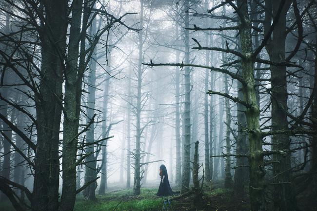 Eine Frau mit Kutte im nebligen Wald.