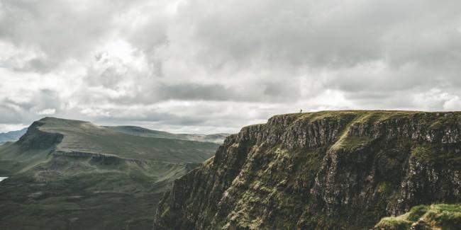 Ein Felsvorsprung auf dem in weiter Ferne eine Person wnadert