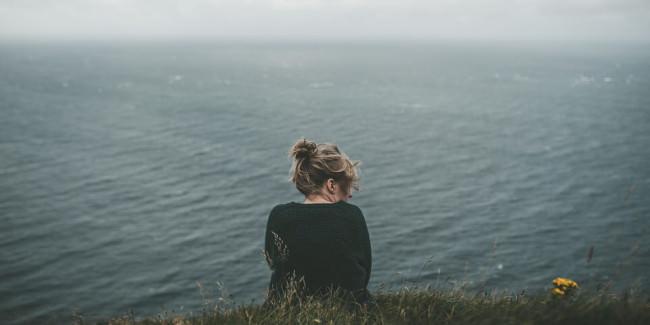 Eine Frau im Gras mit Blick auf das Meer