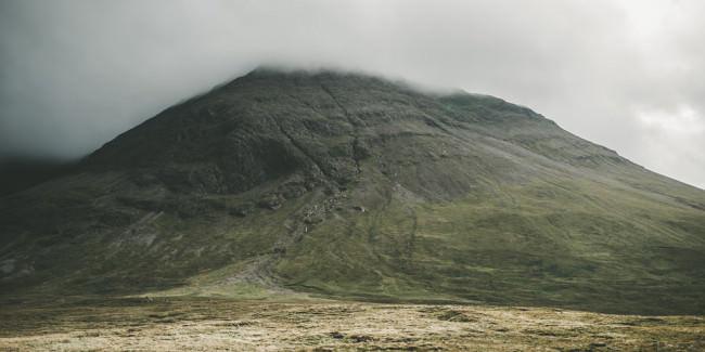 Ein Berg, dessen Gipfel in den Wolken verschwindet.