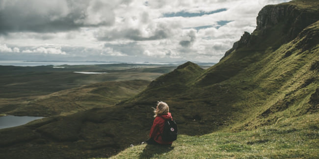Eine Wanderin sitzt auf der Wiese uns sieht ins Land.