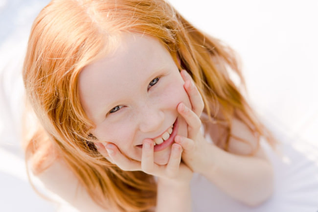 Ein rothaariges Kind lacht in die Kamera.
