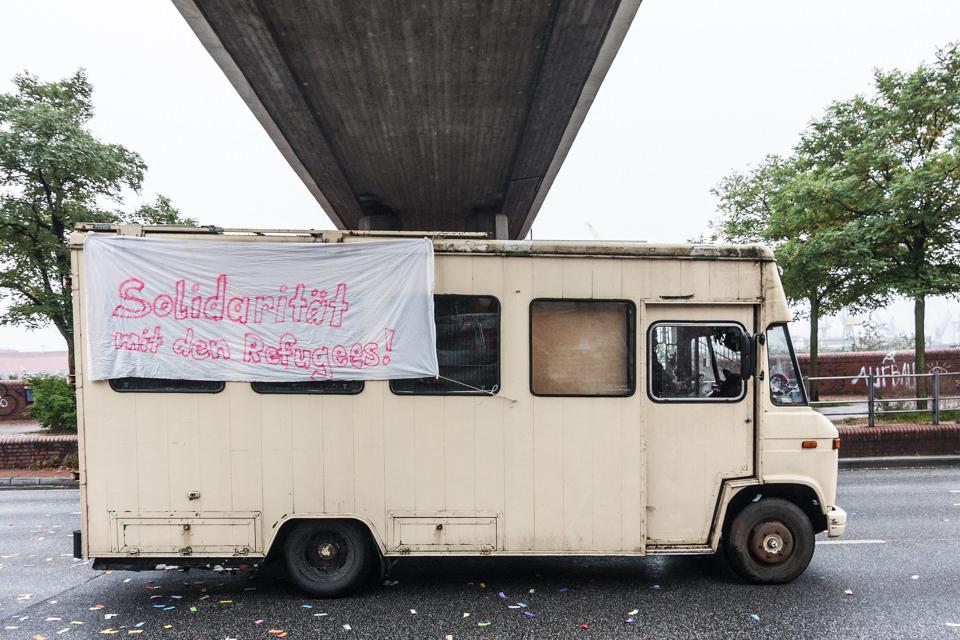 Ein mit Transparenten behangenes Wohnmobil auf einer Demonstration.