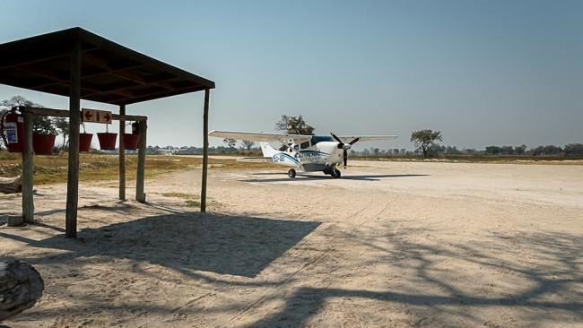 Flugzeug auf einer sandigen Landebahn in der Steppe.