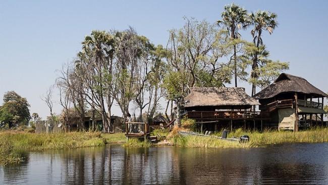 Mehrere Hütten am Rande eines Sees, umgeben von Savanne.