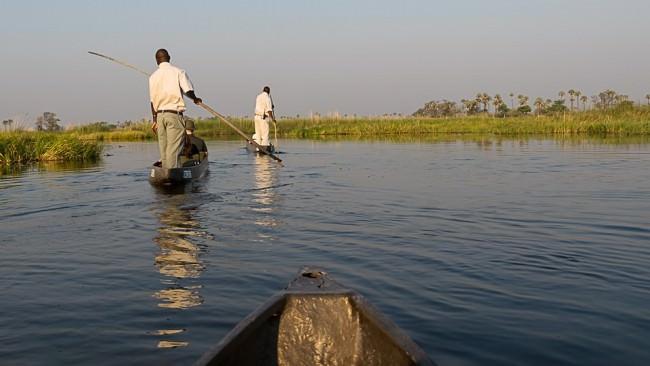 Mehrere Männer in kleinen Booten auf einem Fluss durch die Savanne.
