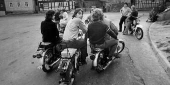 Ein paar Junge Leute auf Mofas und Motorrädern.