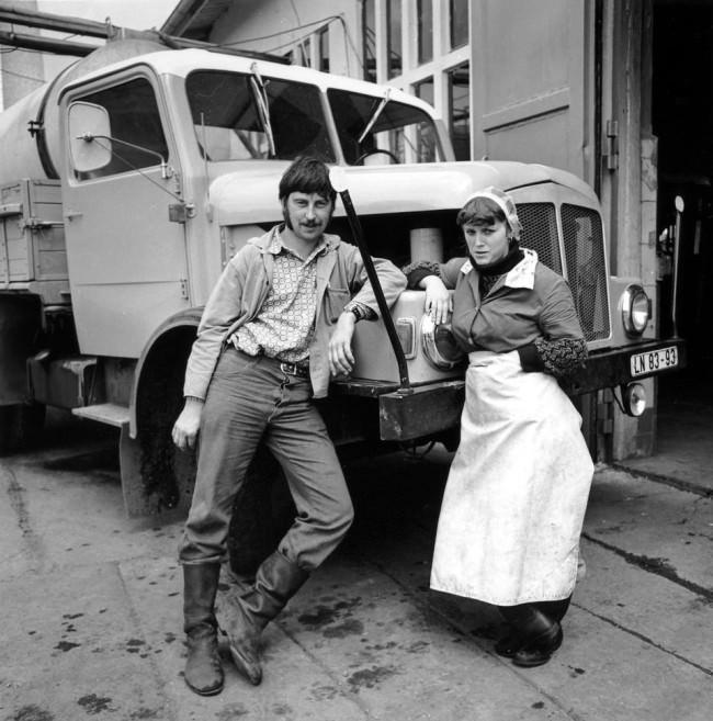 Zwei Arbeiter*innen lehnen locker an der Haube eines LKWs