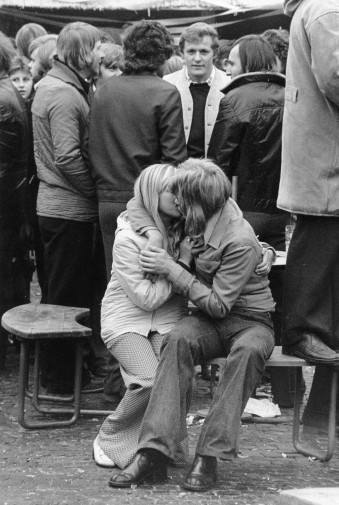 Zwei sich küssende Menschen sitzen vor stehenden Menschen auf einem Stuhl.