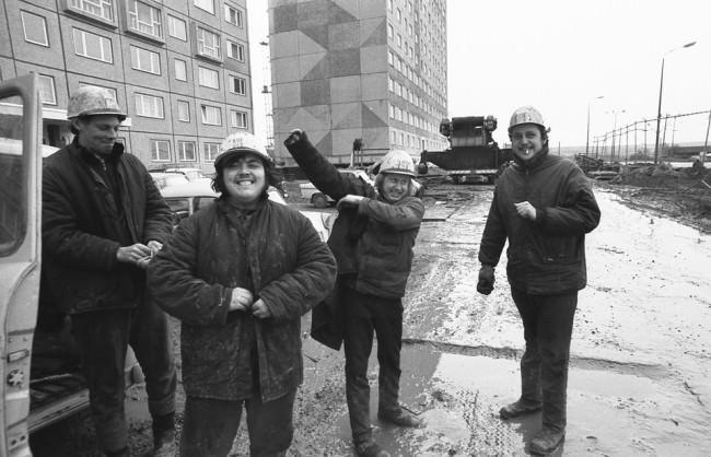 Bauarbeiter lachen in die Kamera.