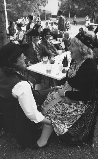 Bei einem Trachtenfest greif ein Mann mit Hut einer Frau unter den Rock