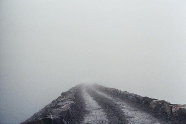 Eine Straße führt in den Nebel.
