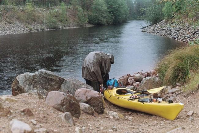 Eine Person an einem Kanu am Ufer bei Regen
